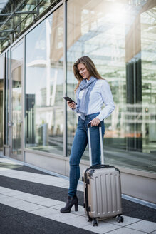 Smiling young businesswoman with suitcase looking at smartphone - DIGF04559