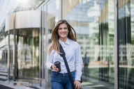 Smiling young businesswoman with bag and coffee to go - DIGF04562
