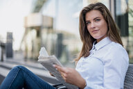Portrait of smiling young businesswoman sitting on bench with newspaper - DIGF04568