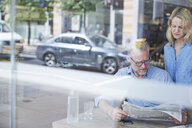 Mature man and woman in cafe, reading newspaper, street reflected in window - CUF21665