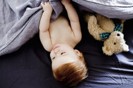 Overhead view of baby girl and teddy bear lying in bed - CUF21716