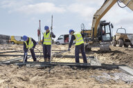 Apprentice builders laying concrete foundations on building site - CUF21827