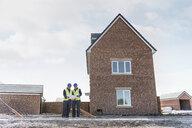 Apprentice builders inspecting site plans on building site - CUF21833