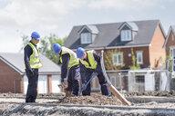 Apprentice builders digging on building site - CUF21836