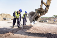 Apprentice builders levelling road with digger on building site - CUF21839
