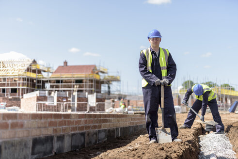 Portrait of apprentice builder laying pipework on housing building site - CUF21854