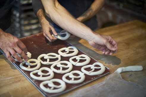 Bakers in bakery preparing fresh pretzls - BEF00117