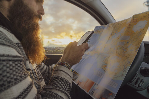 Man using smartphone in car, looking at map for directions - AFVF00615