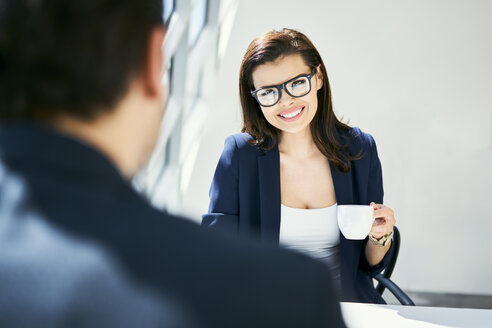 Businesswoman smiling at businessman in modern office - BSZF00458