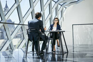 Businesswoman and businessman talking at desk in modern office - BSZF00461