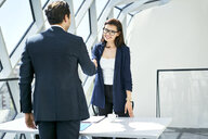 Businesswoman and businessman shaking hands in modern office - BSZF00464