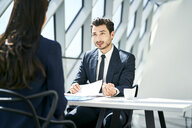 Businessman looking at businesswoman in modern office - BSZF00467