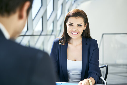 Businesswoman smiling at businessman in modern office - BSZF00470