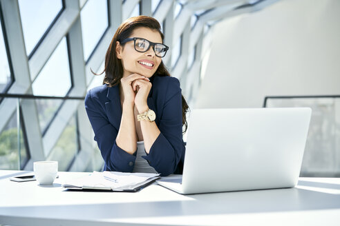 Smiling businesswoman sitting at desk in modern office - BSZF00473