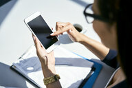 Close-up of businesswoman using cell phone at desk in office - BSZF00479