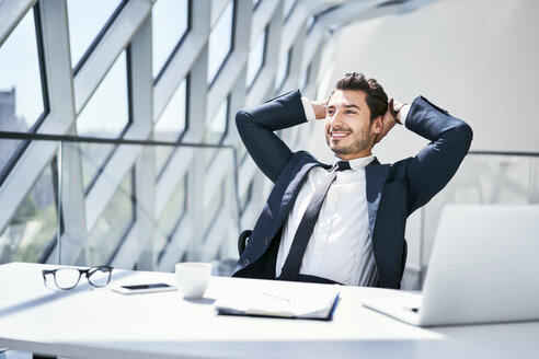 Smiling businessman leaning back at desk in modern office - BSZF00482