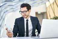 Smiling businessman looking at cell phone at desk in modern office - BSZF00485