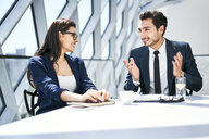 Businesswoman and businessman talking at desk in modern office - BSZF00488