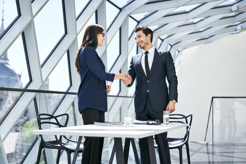 Businesswoman and businessman shaking hands in modern office - BSZF00491