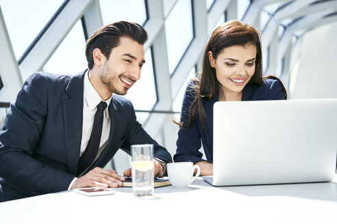 Smiling businesswoman and businessman using laptop at desk in modern office - BSZF00494