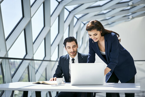 Smiling businesswoman and businessman using laptop at desk in modern office - BSZF00497