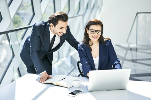 Smiling businesswoman and businessman using laptop at desk in modern office - BSZF00500