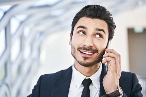 Portait of smiling businessman on cell phone - BSZF00506