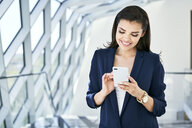 Smiling businesswoman using cell phone - BSZF00515
