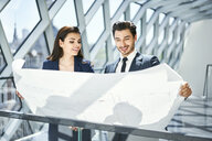 Smiling businesswoman and businessman looking at plan in office - BSZF00521
