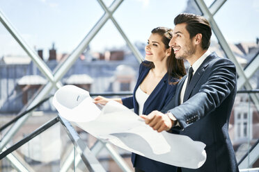Smiling businesswoman and businessman holding plan in office - BSZF00524
