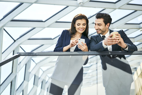Smiling businesswoman and businessman sharing cell phone in modern office - BSZF00527