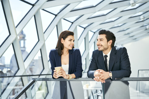 Smiling businesswoman and businessman having a coffee break in modern office - BSZF00530
