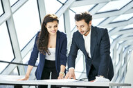 Smiling businesswoman and businessman looking at plan in office - BSZF00536