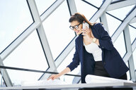 Smiling businesswoman on cell phone looking at plan in office - BSZF00542