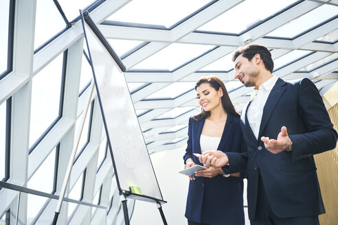 Businessman and businesswoman working with flip chart in office - BSZF00545