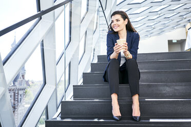 Smiling businesswoman sitting on stairs having a coffee break in modern office - BSZF00548