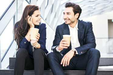 Smiling businesswoman and businessman having a coffee break in modern office - BSZF00551