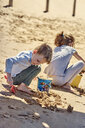 Brother and sister playing with sand on the beach - BEF00130