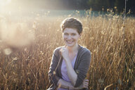 Portrait of smiling woman relaxing in nature - PNEF00639