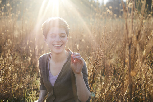 Portrait of laughing woman relaxing in nature - PNEF00645