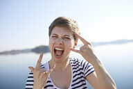 Portrait of screaming woman in front of lake showing Rock And Roll Sign - PNEF00654