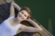 Portrait of smiling woman lying on jetty - PNEF00660