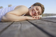 Portrait of laughing woman lying on jetty - PNEF00663