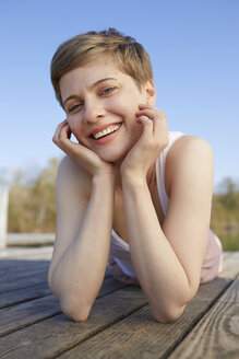 Portrait of smiling woman lying on jetty - PNEF00666