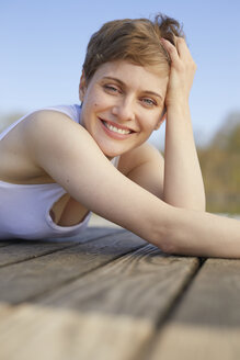 Portrait of happy woman lying on jetty - PNEF00669