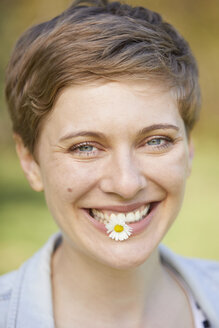 Portrait of laughing woman with daisy in mouth - PNEF00672