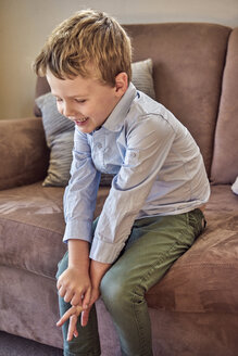 Happy boy sitting on couch - BEF00140