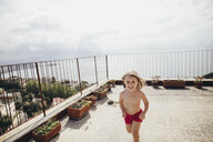Italy, Naples, happy little girl running on roof terrace - KMKF00247