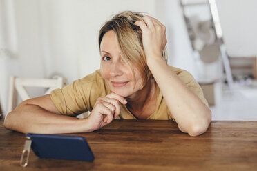 Portrait of smiling woman sitting at table with smartphone in new flat - KMKF00256