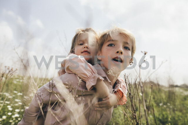 Portrait of boy giving his little sister a piggyback ride - KMKF00262